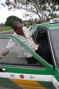 Driver entering Nissan Cedric taxi in Fiji