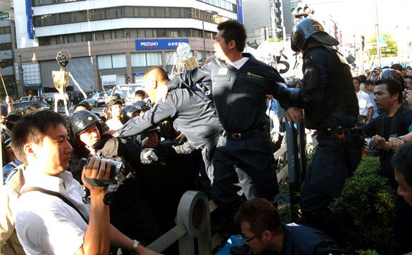 Right-wing members tussle with police during a left-wing march toward Yasukuni Shrine in Kudanshita, Tokyo on Saturday, August 15.