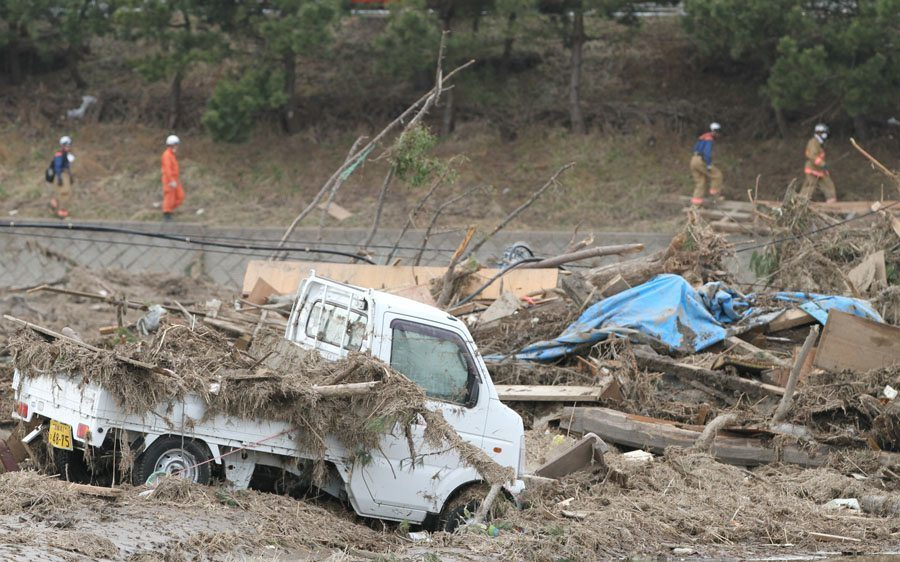 Rescue workers search a field in Wakabayashi Ward