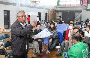 In the Koriyama Junior High School Gymnasium, volunteers receive their assignments.