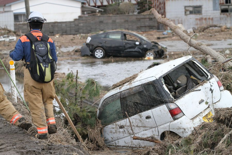 A rescue worker at the edge of a field in Wakabayashi Ward