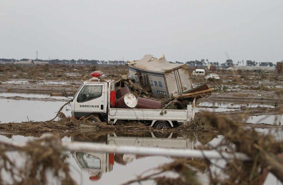 A truck moved by the tsunami sits in a field in Wakabayashi Ward
