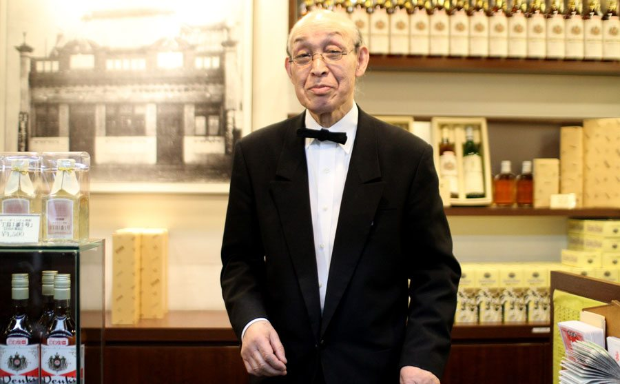 Shopkeeper at Kamiya Bar in Tokyo's Asakusa district displays bottles of Denki Bran, the bar's signature brandy-like drink