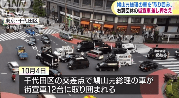 Trucks from the Somokukki no Kai surround ex-PM Hatoyama's car