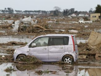 A car moved by the tsunami sits in a field in Wakabayashi Ward