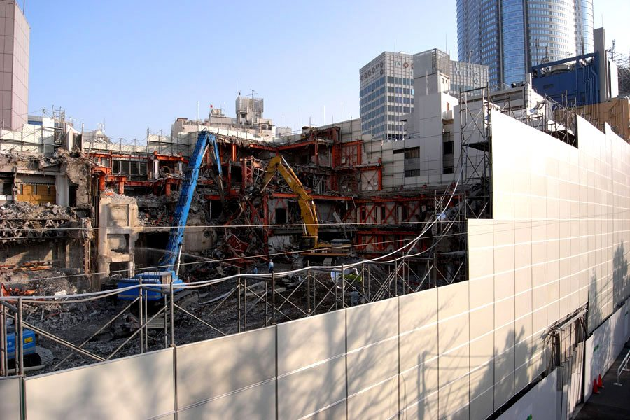 The TSK.CCC building is seen during demolition with Roppongi Hills at right