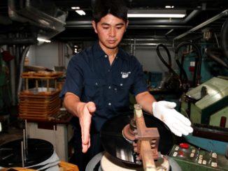 An employee at the Tokyo Kasei factory prepares a disc
